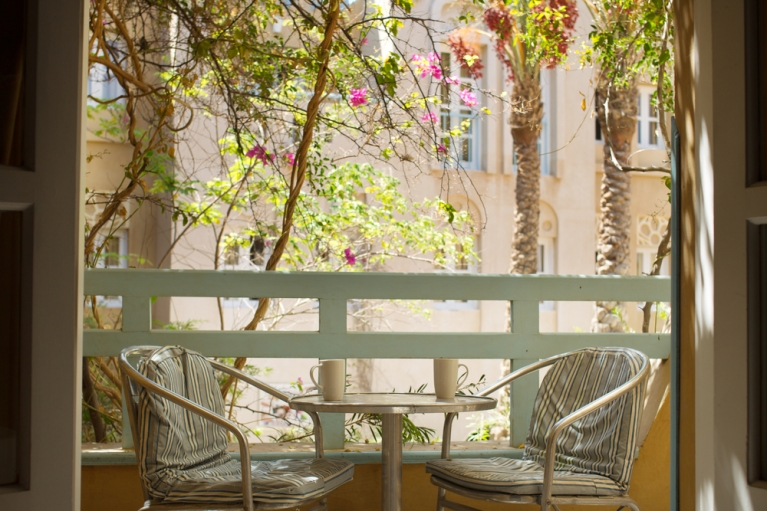 A table and chairs arranged on a balcony with flowers.