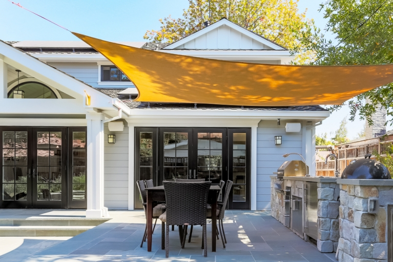 Outdoor eating area protected with a shade sail